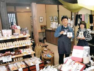 当時のはりを残して修復した店内。岡本さん(左)の前に並ぶのは独自商品の足助塩やクッキーなど=豊田市足助町で