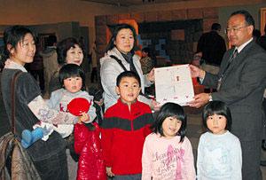 山本館長(右)から記念品を受け取る浅岡さん=県新川文化ホールで