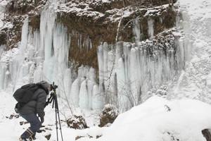 小雪が降る中、氷瀑の造形美を撮影する写真愛好家=茅野市で