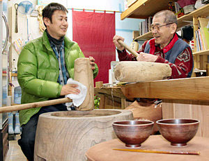 おわん持参の餅つきイベントに向け、道具の手入れをする富田さん(左)=金沢市三馬で