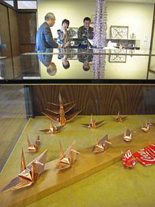 銅板製の折り鶴などが並ぶ会場=となみ散居村ミュージアムで