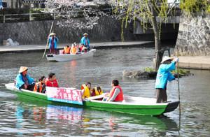 桜を眺めながらの舟下りを楽しむ人たち=大垣市で