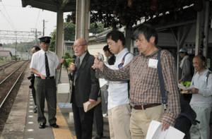 養老駅の特徴などについて解説する伊藤さん(左から2人目)=養老鉄道の同駅ホームで