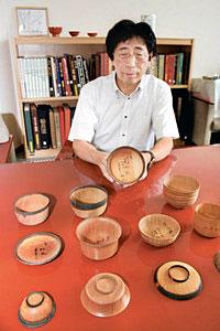 現存最古と見られる椀木地の見本を手にする四柳館長=県輪島漆芸美術館で