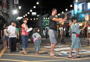 ちょうちんが飾り付けられた特設会場で、伝統の木曽踊りを楽しむ家族連れら=木曽町で