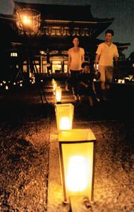 観喜会でライトアップされた境内を歩く参拝者ら=名古屋市中区の東別院で