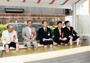 完成した足湯で粟津温泉を楽しむ和田市長(中央)ら=小松市粟津町で