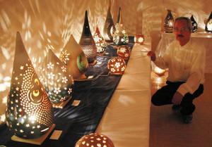 内側から優しい光を出す陶芸作品を紹介する小堀さん=彦根市本町のキャッスルいとーで