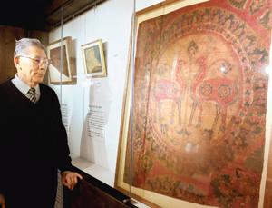 左右対称な絵柄の大きな絹織物などが並ぶ会場=磐田市上野部のシルクロード・ミュージアムで