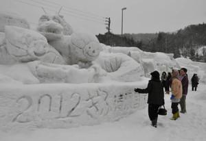 ずらりと並ぶ「ミナモ」などの雪像に見入る人たち=高山市荘川町の道の駅「桜の郷荘川」で