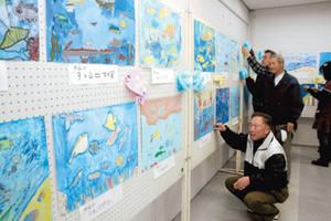 作品の展示作業をするクラブのメンバーら=浜松市北区三ケ日町で
