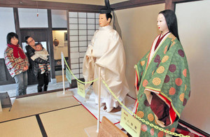 十二単(右)と束帯の衣装に見入る来訪者=大野市の藩主隠居所で