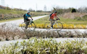 ツインアーチ138をバックに自転車をこぐ人たち=一宮市浅井町河田で