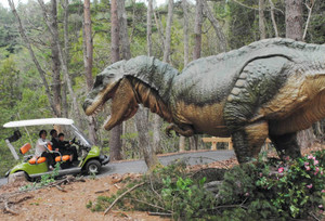 林の中でリアルな動きを見せる恐竜をカートで見て回る参加者=郡上市高鷲町のN・A・O・明野高原キャンプ場で