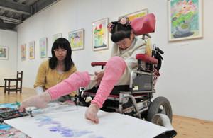 足の指に筆をはさみ、丁寧に絵を描く山口さん(右)=金沢市野町で