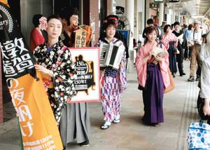 「鉄道と港のまち」をPRするためレトロな衣装を着て商店街を巡る一行=敦賀駅前商店街で