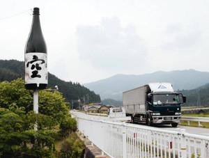 道路脇に立つ巨大酒瓶の広告塔。初めて見る人はびっくり!?=設楽町西納庫の国道257号で(一部画像処理)
