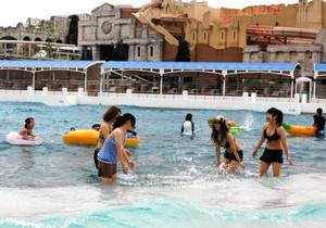 波が立つプールで水しぶきを上げて楽しむ若者ら=蒲郡市のラグーナ蒲郡ラグナシアで