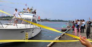 関係者に見送られ、クルーザーに乗って出発する乗船者たち=坂井市の九頭竜川護岸で