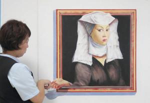 女性の右手が飛び出しているように見えるトリックアート=大垣市高屋町で
