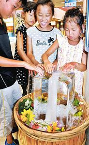 氷柱に触って喜ぶ子どもたち=七尾市府中町で