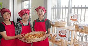 焼きたてのパンを手にする西井さん(中)らアグリ10のメンバー=南砺市蓑谷で