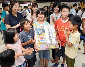 3万人目の入場者となり喜ぶ三嶋さん(中)=金沢市武蔵町で