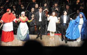 カーテンコールで役者とともにあいさつする山田さん(前列右から2人目)。後列はサイトウ・キネン・オーケストラ=松本市のまつもと市民芸術館で