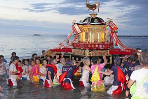 顔に化粧を施すなど女装した若衆に担がれ海へ入るみこし=輪島市の袖ケ浜海水浴場で