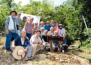 火燈古道(右奥)の登山口に標識を立て、開通を祝う登山愛好家ら=加賀市山中温泉我谷町で