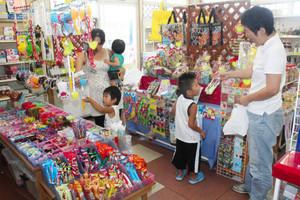 所狭しと商品が並ぶ店内で、子どもに笑顔で話し掛ける北村由紀江さん(右)=尾鷲市新田町で