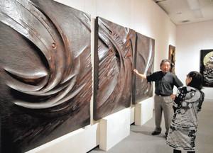 大壁面彫刻「生道への翔」の前に立つ高橋さん(左)=松本市の梓川アカデミア館で