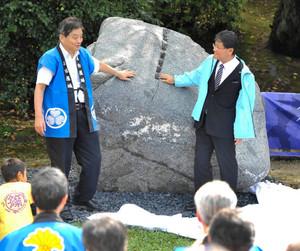 除幕された篠島の矢穴石を触る河村市長(左)と石黒南知多町長=名古屋市中区の名古屋城西之丸広場で