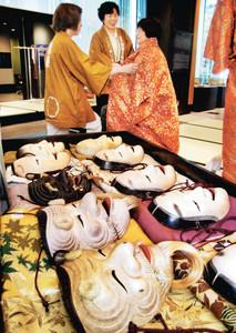 国内外の観光客に人気の体験コーナー。能面を自由に選び、能装束を着て記念撮影もできる=金沢市広坂で