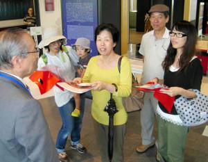 20万人目の入館者となり、藤島館長(左)から記念品を受け取る中村さん=金沢市広坂で
