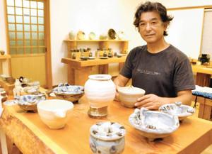 展示会場に益子焼作家らの作品を並べる郷さん=名張市さつき台2番町のぎゃらりー○で