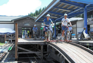 廃線になった旧神岡鉄道の鉄路を走るレールマウンテンバイクを楽しむ利用客=飛騨市神岡町で