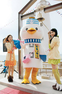 絆の鐘を試しに鳴らす「知多娘。」の声優(両端)と町の観光キャラクター「のまっキー」=美浜町小野浦で