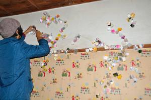 壁に紙を貼って装飾する実行委員=彦根市銀座町の銀座芝居小屋ビルで