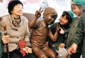 福君の彫像に目を細める唐沢さん(左)とはしゃぐ園児ら=伊那市荒井のタウンステーション伊那まちで