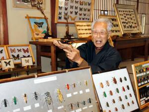 竹を削って作った昆虫を紹介する岡本定男さん=岐阜市大門町の上宮寺で