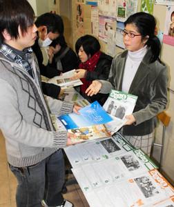 被災地の情報誌の展示会を開いた岩山さん(右)=名古屋市中区の日本福祉大中央福祉専門学校で