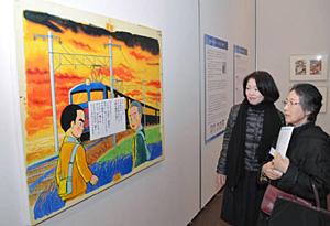藤子不二雄(A)さんが描いた「少年時代」のパネルを鑑賞する来場者=富山市の高志の国文学館で