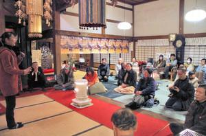 湯本弘美さん(左)の言葉に耳を傾ける参加者たち=越前市の金剛院で