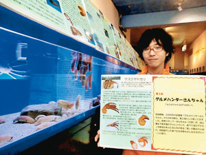 深海生物の試食の記録を発表する三田さん。手前の水槽には「シャコに似た味」のオオグソクムシが泳ぐ=蒲郡市の竹島水族館で
