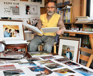 追悼展で展示する学生の写真に目を通す越知専さん=豊橋市小松町で