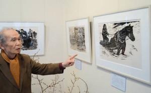 故郷から避難する人々を描いた小口一郎の版画作品が並ぶ会場=長野市川中島町今井の「ひとミュージアム上野誠版画館」で