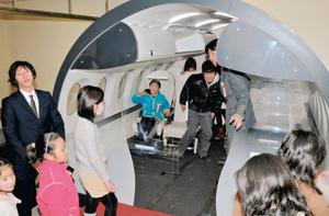 常設展示された模型の客室空間を体験する子どもたち=豊山町の県営名古屋空港で