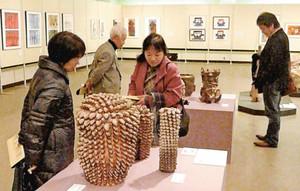 熱心に作品を見つめる来場者たち=長浜市大島町の長浜文化芸術会館で