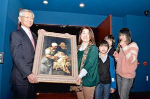 来場者数1万人を記念し、北陸銀行の高木頭取(左)から絵画を受け取る立花さん家族ら=富山市中央通りで